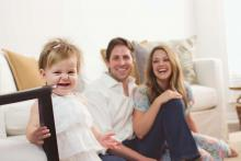 Happy toddler with parents by Sunny Mays